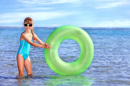 Children holding inflatable ring in sea. Stock Photo