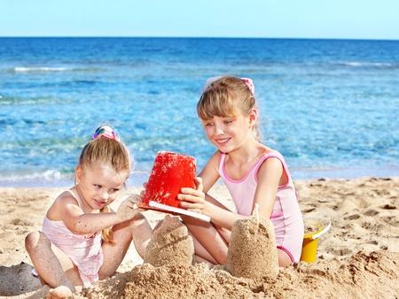 arena: Niña jugando en la playa. Foto de archivo