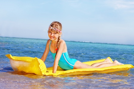 one piece swimsuit: Little girl swimming inflatable beach mattress. Stock Photo