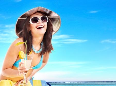 beach drink: Girl in bikini drink juice through a straw. Stock Photo