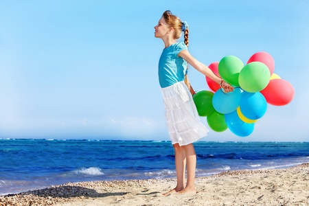 little girl playing with balloons at the beach. photo