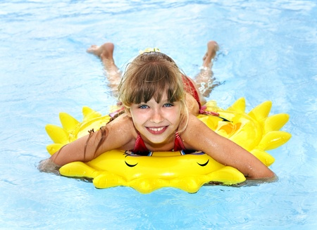 little girl smiling: Children  on inflatable ring in swimming pool.