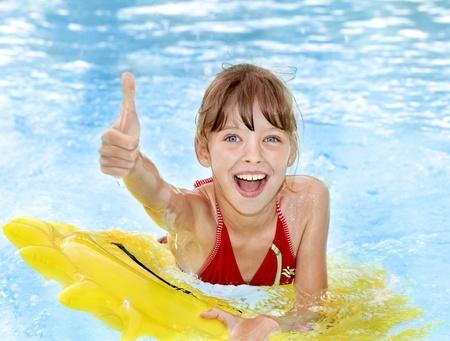 meisje zwemmen: Kinderen zittend op opblaasbare ring in zwembad.