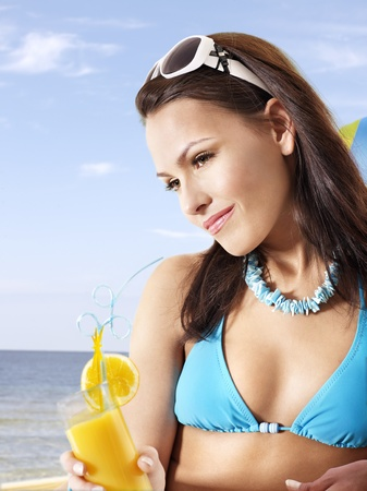 Girl in bikini drink juice through a straw. photo