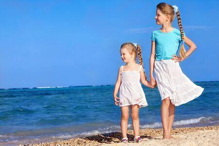 niños caminando: Niños tomados de la mano, caminando en la playa. Vista posterior.