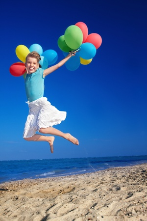 little girl playing with balloons at the beach. Stock Photo - 8942346