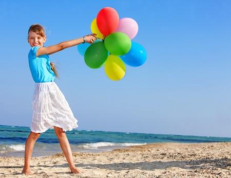 niñas jugando: niña jugando con globos en la playa.