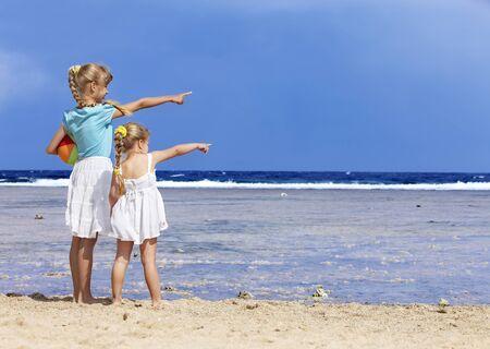 klein meisje op strand: Meisje op het strand met de bal spelen.