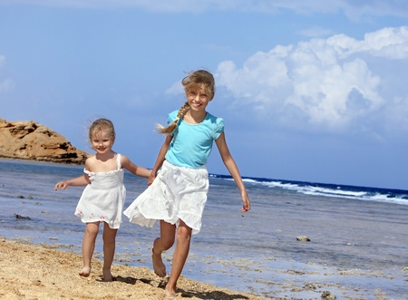 Children holding hands walking on the beach. Rear view. photo