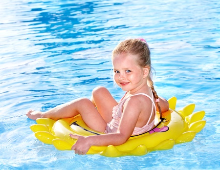 one piece swimsuit: Children  on inflatable ring in swimming pool.