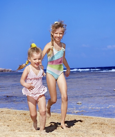 one piece swimsuit: Children holding hands walking on the beach. Rear view.