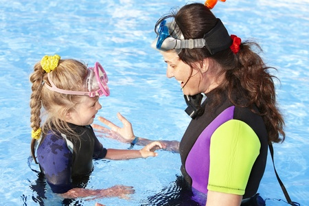 scuba woman: Child with mother in swimming pool learning snorkeling.