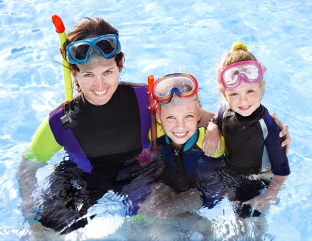 Children with mother  in swimming pool learning snorkeling. photo