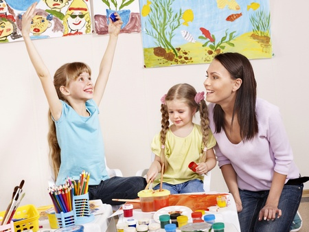 kids painting: Children painting in preschool. Teacher help by little girl. Stock Photo