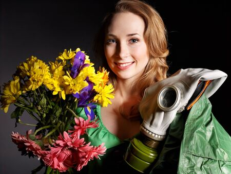 chemical warfare: Young woman holding flowers and gas mask .