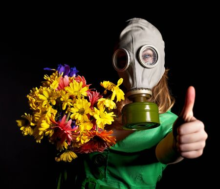 Thumb up of young woman  in gas mask and flowers.   photo