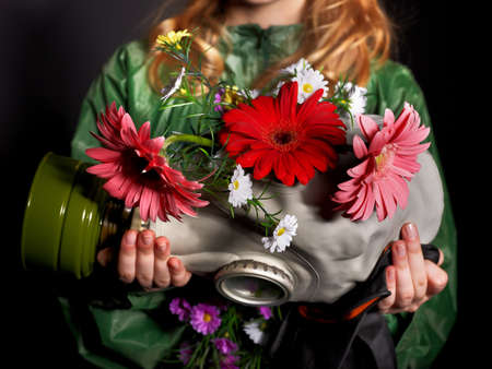 gasmask: Female hands holding  gas mask with flowers . Stock Photo