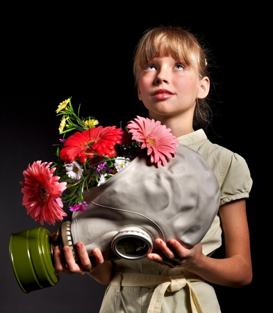 Little girl holding flowers and gas mask . Stock Photo - 8941800