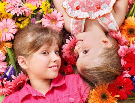 Little cute girl lying head to head on the flower. photo