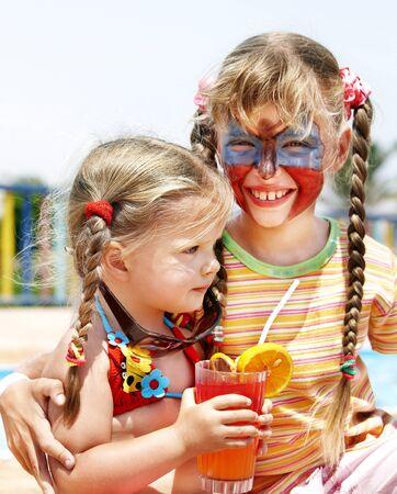 maquillaje infantil: Jugo de ni�os con beber de la pintura en la cara naranja.  Foto de archivo
