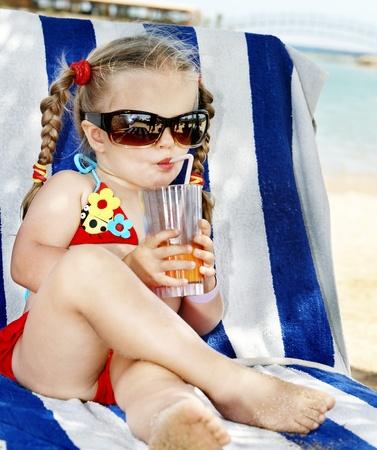 Little girl in glasses and red bikini drink orange juice. photo