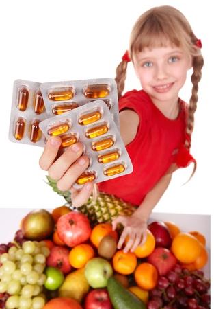 vitamina a: Ni�o con frutas y vitamina p�ldora. Aislado.
