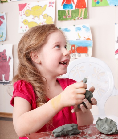 sculp: Little girl moulding from clay in play room. Stock Photo