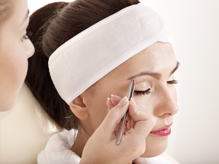 plucking: Tweezing eyebrow by beautician. Isolated. Stock Photo