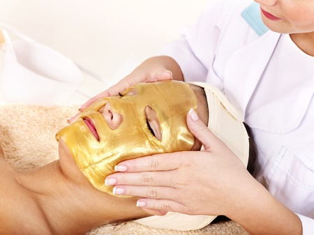 masked woman: Young womanl with gold facial mask. Stock Photo