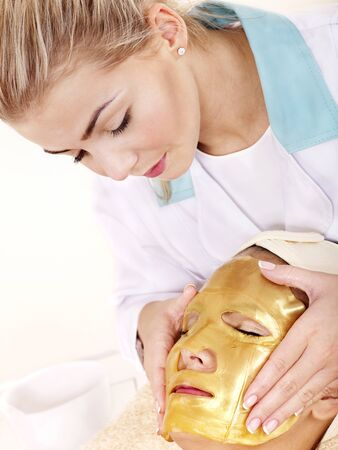 Young woman with gold facial mask. photo