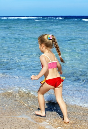 Child  walking on the beach. Rear view. photo