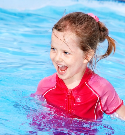 Little girl  swimming in pool. photo