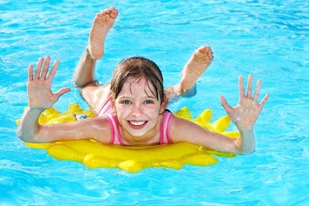 Bambino su anello gonfiabile in piscina.