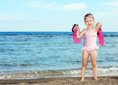 wetsuit: Little girl  playing on  beach.