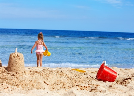 bucket and spade: Little girl  playing on  beach.