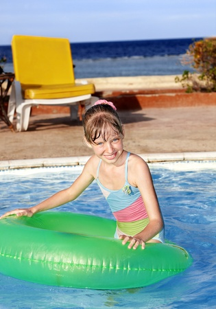 Children sitting on inflatable ring in swimming pool. Stock Photo