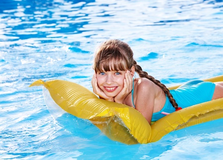 Little girl swimming on inflatable beach mattress.