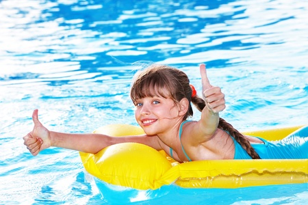 Child sitting on inflatable ring in swimming pool. Stock Photo - 9268117