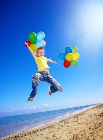 meisje met ballonnen spelen op het strand. Stockfoto