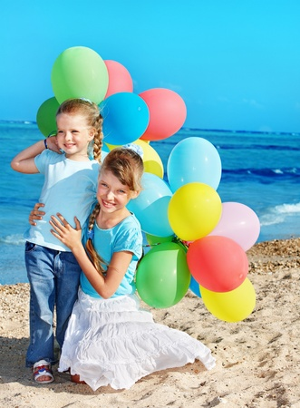 little girl playing with balloons at the beach. Stock Photo - 9268227