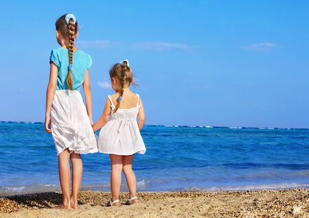 backview: Children holding hands walking on the beach. Rear view.