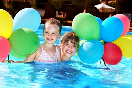 kids playing water: little girl playing with balloons in swimming pool.