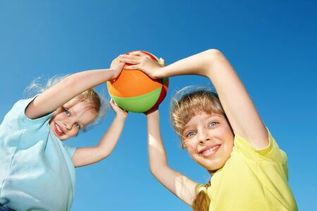 Children playing with ball aganist blue sky.  Outdoor. photo