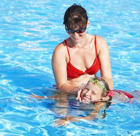 Instructor girl learn child swim in swimming pool. photo