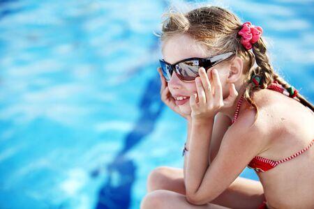 Child girl in red bikini and glasses near blue swimming pool. Summer.