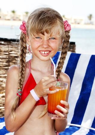 Little girl on beach drinking cocktail. photo