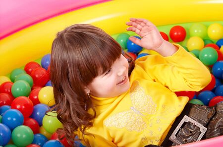 Little girl playing  in group colourful ball. photo