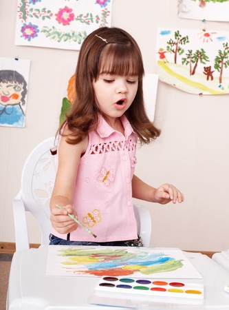 Little girl paint picture in preschool. Child care. photo