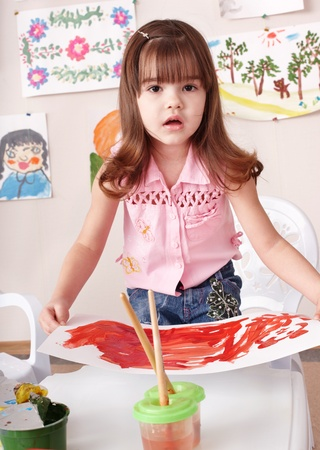 Little girl painting picture in art class. photo