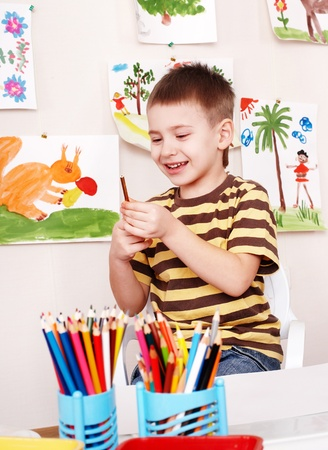 nurser: Little boy with pencil in play room.